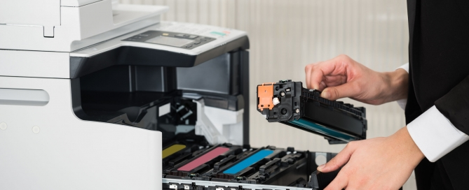 Midsection of young businessman fixing cartridge in printer machine at office