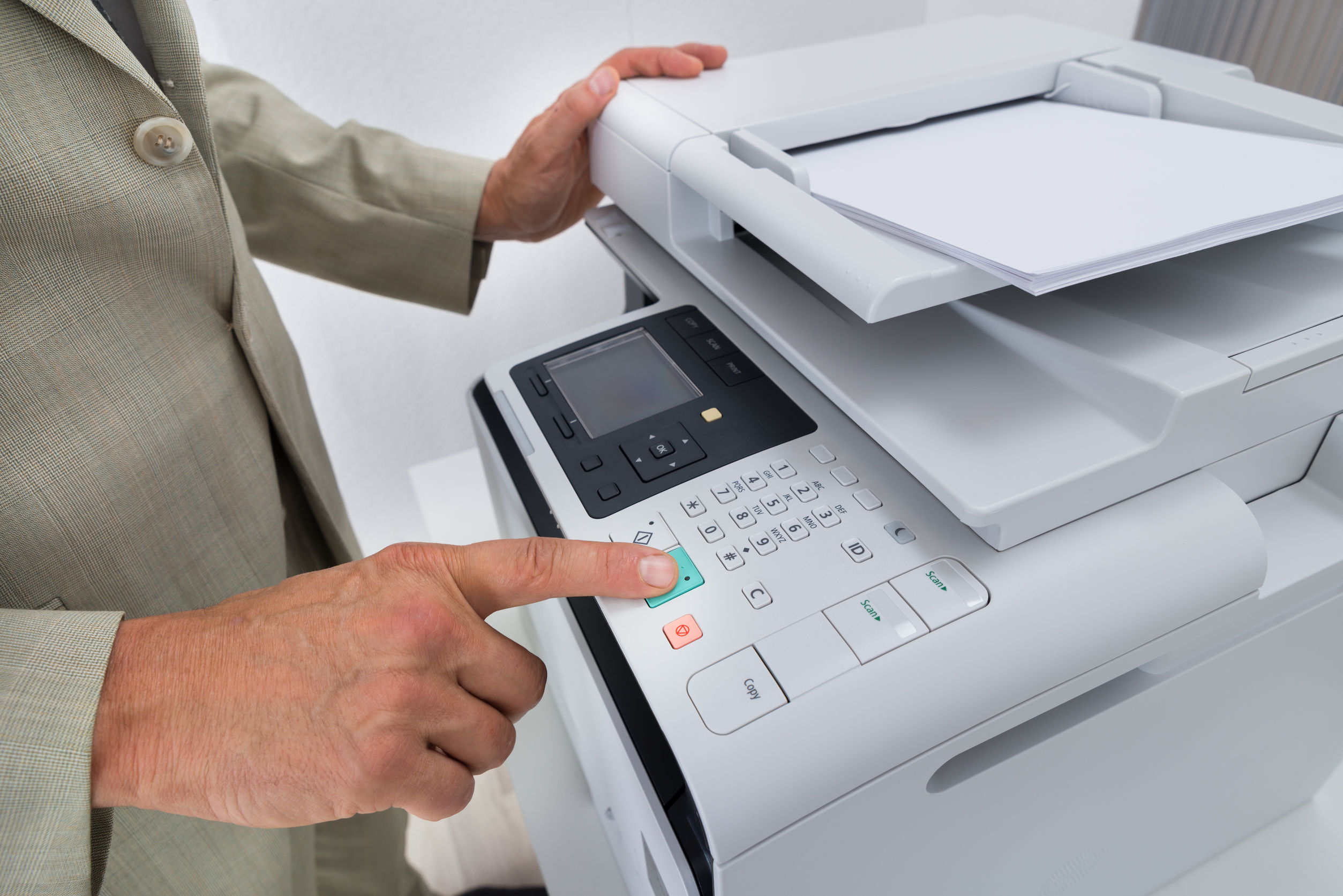 Midsection side view of businessman pressing printer's button in office